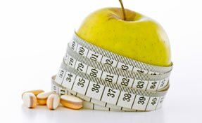 Apple wrapped with measuring tape next to vitamins